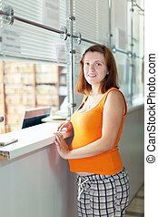 Pregnant woman waiting  for patient's records in clinic