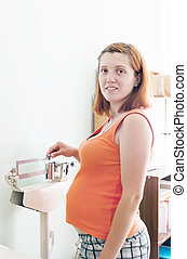 Pregnant woman weighing on  scales