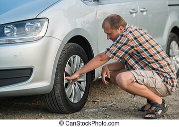 checking tire - young man checking tire of siver car