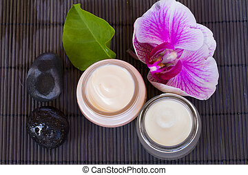 orchid flower and beauty creams with spa stones