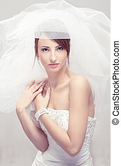 Bride in white veil looking at camera. Portrait. Fashion wedding shot.