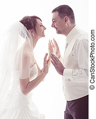 Bride and groom face-to-face holding hands over white...