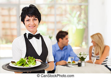 pretty middle aged waitress working in restaurant