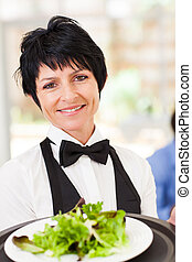 elegant mid age waitress serving salad in restaurant