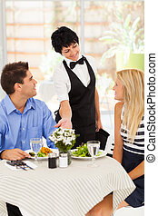 waitress serving customers in cafe - happy waitress serving...