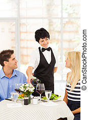 friendly mature waitress serving wine to diners in...