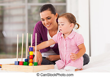 little girl playing educational toy with mother on bed