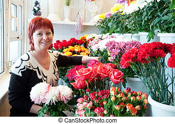 woman in flowers store - woman in the shop surrounded by...