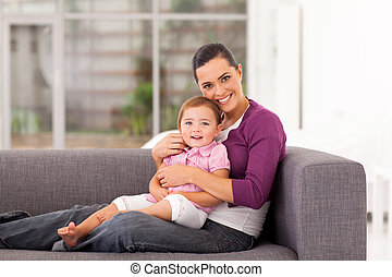 happy mother hugging daughter on sofa