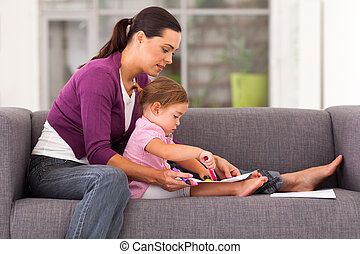mother teaching daughter drawing