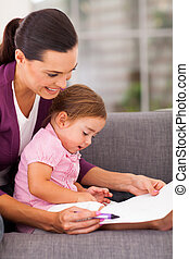 mother teaching little daughter drawing