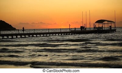 People walking on pontoon at sunset - People walking on a...