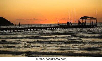 People walking on pontoon at sunset