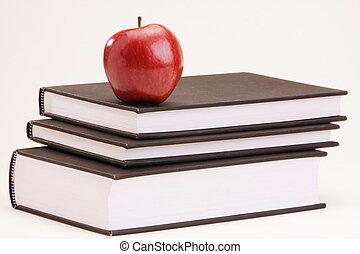 An apple placed on top of books - An apple placed on top of...