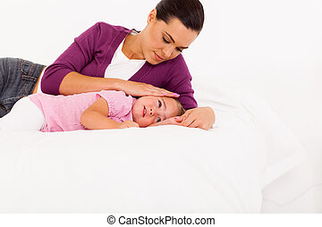 caring mother comforting crying baby girl on bed