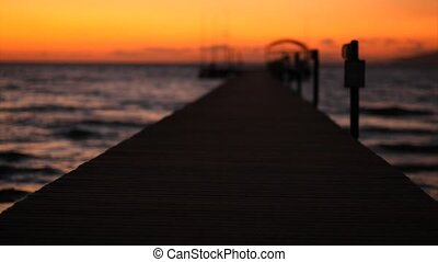 Sunset over sea and pontoon - Wooden pontoon in and out of...