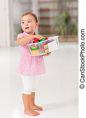 cute little girl holding box of toy