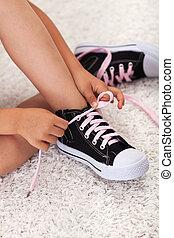 Child hands tie shoelaces - closeup