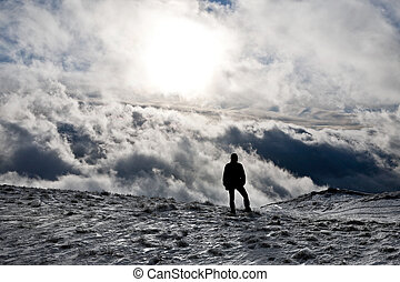 Man with cloudy background - Silhouette of a man standing on...