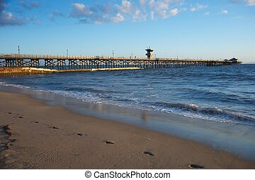 Huntington Beach Pier and sandy beach sunset