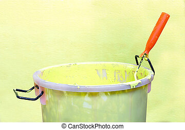 Paint-roller and Paint bucket with paint on a green...