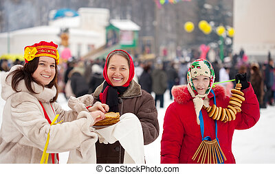 Women eating pancakes during Shrovetide festival in Russia