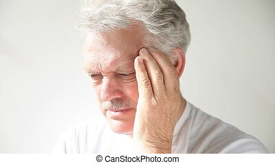 headache pain - senior man rubs his temples as he suffers...