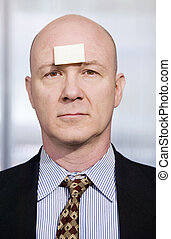 Businessman with a blank note on her forehead