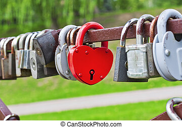 Red heart-shaped padlock between the other padlocks