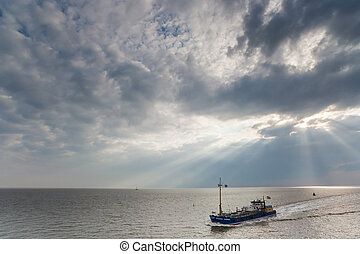 Fishing boat in sun breaking through