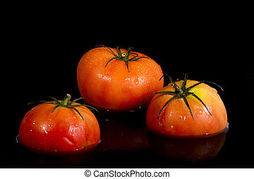 three red tomatoes on a black background