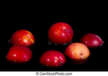red plums on a black background