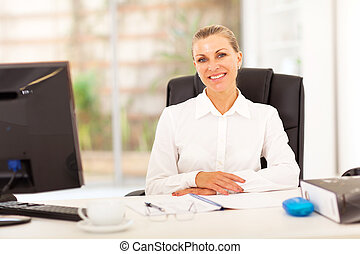 senior businesswoman sitting in front of desk in office
