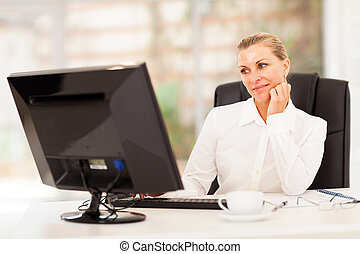 thoughtful senior businesswoman in front of computer