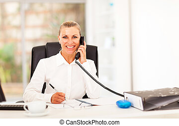 happy senior businesswoman talking on the phone in office