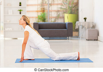 mature woman doing yoga at home