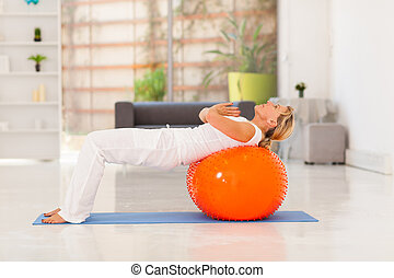 mature woman working out with exercise ball at home