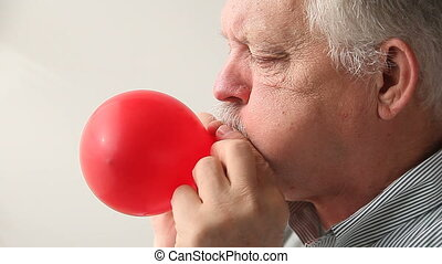 man blowing up balloon