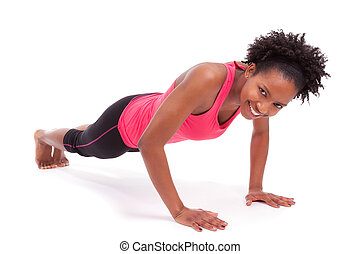 Young beautiful african fitness woman doing push up exercises on floor,isolated on white background