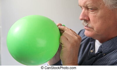 man lets air out of balloon