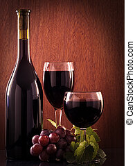 Red wine glass and bottle on a wooden background Low key...