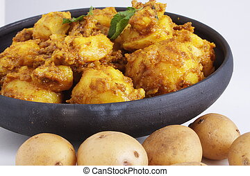 Cooked potatoes besides raw ones - Garnished dum aloo subji,...