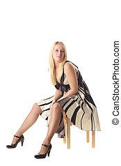 Girl on stool - Girl in dress sitting on stool over light...