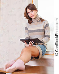 woman reads e-reader - Young woman reads e-reader at home...
