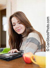 Young woman reads e-reader at home