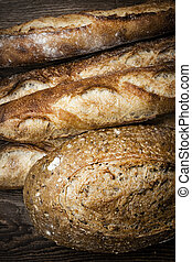 Artisan bread - Fresh baked rustic bread loaves on dark wood...