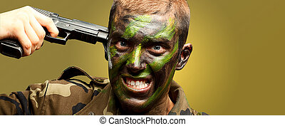 Soldier Putting Gunshot On Head against a yellow background
