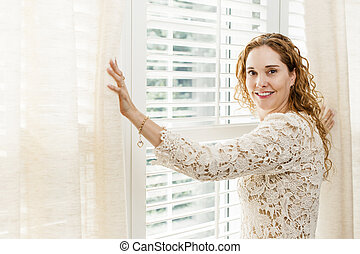 Smiling woman near window - Happy woman opening curtains on...