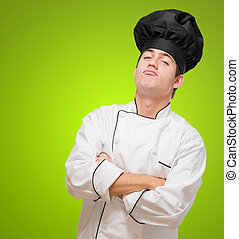 Portrait Of A Funny Chef With Hands Folded against a green...