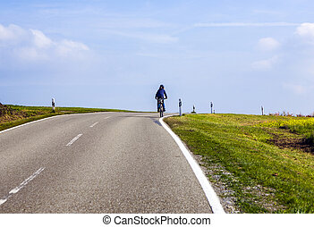 young boy on tour with the bike in rural area